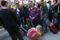 Activists pull luggage in their sarcastic protest. Photo: David Wong