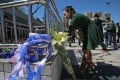 A woman places flowers for the victims along a fence outside the railway station. Photo: EPA