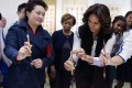 Peng Liyuan shows Michelle Obama how to hold a writing brush as they visit a Chinese traditional calligraphy class at the Beijing Normal School. Photo: Reuters