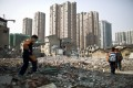 Pupils walk in an area where old residential buildings are being demolished to make room for new skyscrapers in downtown Shanghai, March 14, 2014. Photo: Reuters