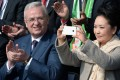 Peng Liyuan, wife of the president of the People's Republic of China, Xi Jinping, takes pictures next to Volkswagen CEO, Martin Winterkorn in Berlin, Germany on Saturday. Photo: AP