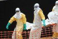 Medecin Sans Frontieres staff carry the body of a person killed by Ebola at a treatment centre in Guekedou, Guinea. Photo: AFP
