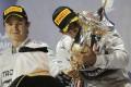 Nico Rosberg looks on as Lewis Hamilton kisses the trophy. Photo: Reuters