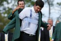Masters champion Bubba Watson of the US  is helped with his traditional green jacket by last year's champion Adam Scott. Photo: Reuters