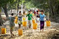 Residents of Dala, near Yangon, carry plastic containers filled with drinking water fetched from a natural pond. Photo: AP