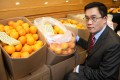 Customs' intellectual property officer Lam Yau-tak shows off some of the haul of fake Sunkist oranges. Photo: SCMP Pictures