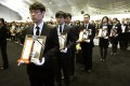 Funeral service employees carry portrait of victims of the sunken ferry Sewol at the official memorial altar in Ansan. A probe into the disaster has heard that warnings over the ship's seaworthiness were ignored. Photo: Reuters