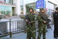 Armed police officers standing guard at the Urumqi South railway station. Photo: Reuters