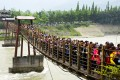 Tourists swarm onto a suspended bridge at the Dujiangyan heritage site in Sichuan province. Photo: China Foto Press