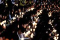 High school students hold candles during a rally to pay tribute to the victims and missing passengers of the sunken ferry Sewol in Ansan, South Korea on Friday. Photo: AP