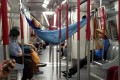 No one seems to notice as this brazen passenger takes a doze in a hammock strung between the seats of an Island Line train on Monday night. Photo: SCMP Pictures