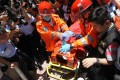 Paramedics treat the injured suspect as he is brought out of Lok Ching House and rushed to hospital. Photo: Edward Wong