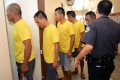 A Philippine prison guard escorts nine arrested Chinese fishermen as they arrive at a courtroom for a pre-trial in Puerto Princesa City, Palawan. Photo: AFP