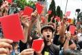 Demonstrators hold up red cards to show their disapproval of Zhang Zhijun. Photo: AFP