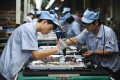 Young migrant workers labour on a television set assembly line in a factory in Shenyang, Liaoning Province. Photo: EPA