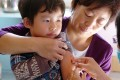 A child receives measles vaccine. Measles is making a comeback in China as millions of migrant workers miss out on vaccinations. Photo: Xinhua