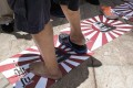 A protester steps on illustrations of Japanese military flags featuring a portrait of Hideki Tojo, general of the Imperial Japanese Army and prime minister of Japan during most of World War Two, at a rally against Japanese Prime Minister Shinzo Abe's push to expand Japan's military role abroad, near the Japanese consulate in Hong Kong