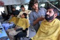 Internally displaced Pakistan civilians fleeing from a military operation against Taliban militants receive haricuts in Bannu. Hundreds of Taliban fighters rushed to disguise themselves with new haircuts. Photo: AFP