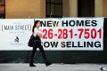 A pedestrian walks past an advertising banner for new home sales in Alhambra, California. Photo: AFP