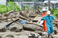 Workers walk among debris at an area affected by landslide caused by heavy rains due to Typhoon Neoguri in Nagiso. Photo: Reuters