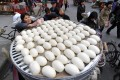 A vendor takes steamed buns for customers at a mainland market. This and other breakfast staples are the cheaper and sometimes only option for working-class families in Haidian. Photo: Reuters