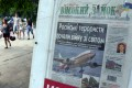 People walk in Lviv, passing a newsstand with newspaper depicting flight MH17. Photo: AFP