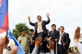 Cambodian opposition leader Sam Rainsy greets supporters on his return from France after eight politicians from his party were arrested and charged with insurrection over a protest that turned violent. Photo: AFP