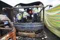 Police inspect the inside of the burned-out bus on the Hukun Expressway after it was hit by a van carrying flammable liquid. Photo: Xinhua
