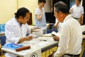 A local resident receiving a dose of iodine tablets from a Kagoshima prefectural officer in the city of Satsumasendai, Kagoshima, Kyushu. Photo: AFP