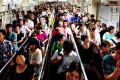 Commuters wait to enter a subway station during the morning rush hour in Beijing. Photo: AFP