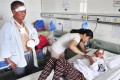 A woman tends to one of the victims of the wolf attack in Xinjiang, as another bandaged victim looks on. Photo: Reuters