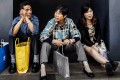 Mainland shoppers sit in front of a shop selling luxury goods in Hong Kong. Photo: AFP