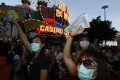 """Workers from Macau's six major casinos, led by union """"Forefront of Macau Gaming"""", chant slogans as they march past SJM-owned Casino Lisboa on Tuesday. Photo: Reuters"""