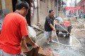 Residents wash a rug with water from illegal well. Photo: SCMP