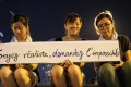 """Three students holding a banner that reads """"Soyez réaliste, demandez l'impossible"""" (Be realistic, demand the impossible), a slogan from the Mai 1968 student movement in France, during pro-democracy demonstrations in Hong Kong on Monday. Photo: AFP"""