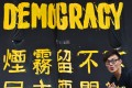 A pro-democracy protester stands next to a banner in Hong Kong. Photo: AFP