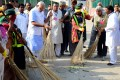 Prime Minister Narendra Modi (left) sweeps a street in a poor area of New Delhi yesterday as part of the national clean-up. Photo: AFP