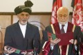 Ashraf Ghani (left) takes an oath of office as Afghanistan's new president in Kabul on September 29, 2014.