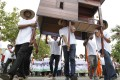 Cambodians carry a model of a house during a rally in Phnom Penh to protest against widespread land evictions. Photo: EPA
