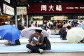 Protesters sit outside a Chow Tai Fook store in Causeway Bay. Photo: Bloomberg