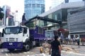 A crane is used to scoop up metal barriers and dump them into a truck in Admiralty. Photo: Jeffie Lam