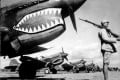 In this 1943 photo, guarded by a Chinese soldier, a squadron of Curtiss P-40 fighter planes, decorated with the typical shark face of the famed Flying Tigers, are lined up at an unknown airbase in China. An airfield in southern China from which the famed Flying Tigers took off to fight Japanese warplanes is being converted to battle a new enemy: drought. Photo: AP