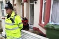 A police officer stands outside a house in Portsmouth, southern England. British police arrested three men and three women on Tuesday in a counter-terrorism operation linked to the civil war in Syria. Photo: Reuters
