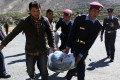 Nepalese police carry a trekker's body to a plane. Photo: AFP