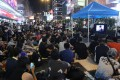 Protesters in Mong Kok watch live coverage of the talks between government representatives and student protest leaders. Photo: Dickson Lee