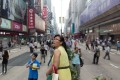 A woman stands on the central barrier on Nathan Road, where most shops were closed. Photo: Bloomberg