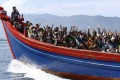 Ethnic Rohingya refugees from Myanmar wave as they are travel on a wooden boat. Photo: Reuters