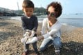 Tak Cheng, three, of Banyan House preschool and his mother, Maeve Cheng, participate in a clean-up at Yung Shue Wan beach. Photo: Nora Tam