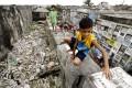 Children play near human bones in a Manila cemetery. Photo: EPA