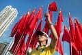 A man holds up a Chinese national flag as he sings the national anthem at an event to celebrate the 65th anniversary of the founding of Communist China at Victoria park in Hong Kong. Photo: AFP